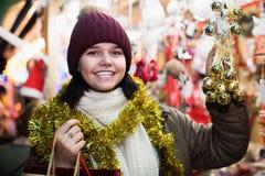 Glückliches jugendlich Mädchen, das Geschenke an der festlichen Messe wählt Stockbild