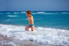 Glückliches Jungenkind, das Spaß im Meerwasser hat Stockbild