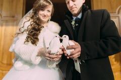 Glückliches junges verheiratetes Paar, das zwei weiße Tauben als Symbol des Friedens in den Händen hält Stockfotos