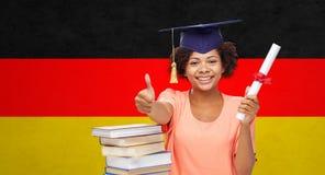 Glückliches Junggesellemädchen mit dem Diplom, das sich Daumen zeigt Lizenzfreies Stockfoto