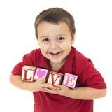 Glückliches Kind buchstabiert LIEBE Stockfotos