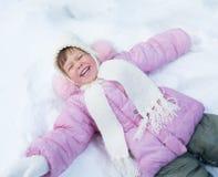 Glückliches Kind, das auf Schnee im Winter im Freien liegt Stockbilder