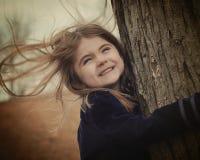 Glückliches Kind, das Baum im Wind hält Stockfoto