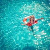 Glückliches Kind, das im Swimmingpool spielt Stockfotos