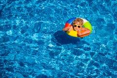 Glückliches Kind, das im Swimmingpool spielt Stockbild