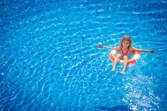 Glückliches Kind, das im Swimmingpool spielt Lizenzfreies Stockfoto