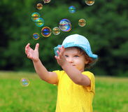 Glückliches Kind, das mit Blasen spielt Stockbild