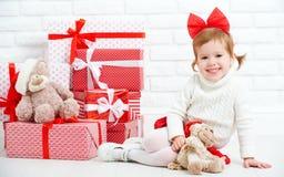 Glückliches Kind des kleinen Mädchens mit Weihnachtsgeschenken an der Wand Lizenzfreies Stockbild