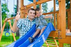Glückliches Kind und Vater, die Spaß hat Kind mit dem Vatispielen Stockfoto