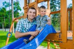 Glückliches Kind und Vater, die Spaß hat Kind mit dem Vatispielen Stockbild