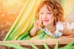 Glückliches Kindermädchen, das in der Hängematte im Sommer sich entspannt Stockbilder