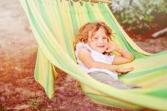Glückliches Kindermädchen, das in der Hängematte im Sommer sich entspannt Stockbild