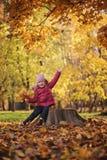 Glückliches Kindermädchen, das mit Herbstlaub auf dem Weg am sonnigen Herbsttag spielt Stockfoto