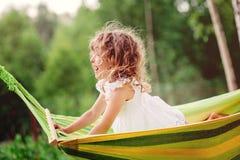 Glückliches Kindermädchen, das Spaß hat und in der Hängematte im Sommer sich entspannt Stockbilder