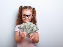 Glückliches Kindermädchen in den Gläsern, die Geld in der Hand und im Schauen halten Stockbild