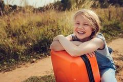 Glückliches Kindermädchen mit dem orange Koffer, der allein auf Sommerferien reist Kind, das zum Sommerlager geht Stockbilder