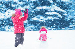 Glückliches Kindermädchen mit einem Schneemann auf einem Winterweg Stockbild