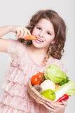 Glückliches Kinderporträt mit organischem Gemüse, kleines lächelndes Mädchen, Studio Stockbild