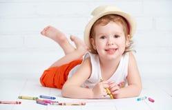 Glückliches kleines Künstlermädchen in einem Hut zeichnet Bleistift Stockfotos