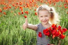 Glückliches kleines Mädchen auf der Mohnblumenwiese, die Daumen aufgibt Lizenzfreie Stockbilder