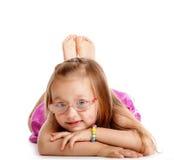 Glückliches kleines Mädchen, das auf den Boden lokalisiert legt Lizenzfreies Stockfoto