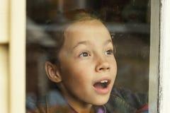 Glückliches kleines Mädchen, das durch ein altes Fenster schaut Stockfotos