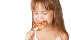 Glückliches kleines Mädchen, das eine Lutschersüßigkeit isst Stockfotografie