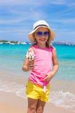 Glückliches kleines Mädchen, das Eiscreme über Sommerstrandhintergrund isst Lizenzfreie Stockfotos