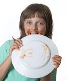 Glückliches kleines Mädchen, das etwas Lebensmittel isst Stockfoto
