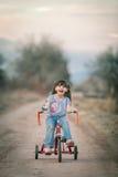 Glückliches kleines Mädchen, das ihr Dreirad reitet Lizenzfreies Stockfoto