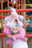 Glückliches kleines Mädchen, das ihr Lieblingsspielzeug umarmt Stockfotos