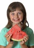 Glückliches kleines Mädchen, das Melone isst Stockfoto