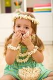 Glückliches kleines Mädchen, das Popcorn isst Lizenzfreies Stockfoto
