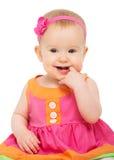 Glückliches kleines schlaues Baby im hellen mehrfarbigen festlichen Kleid Stockfotos