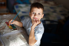 Glückliches kleines Vorschülerjungen-Malereimalbuch Stockfoto