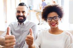 Glückliches kreatives Team im Büro, das sich Daumen zeigt Lizenzfreies Stockbild