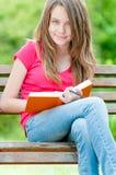 Glückliches Kursteilnehmermädchen, das auf Bank mit Buch sitzt Lizenzfreies Stockfoto