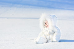 Glückliches lachendes Baby im Schnee am sonnigen Wintertag Lizenzfreies Stockbild
