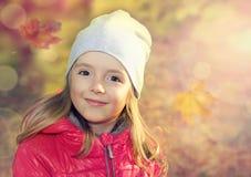 Glückliches lächelndes Kind draußen auf Fallhintergrund Lizenzfreies Stockfoto