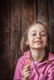 Glückliches lächelndes Kindermädchen mit Lutscher auf rustikalem hölzernem Hintergrund Lizenzfreies Stockbild