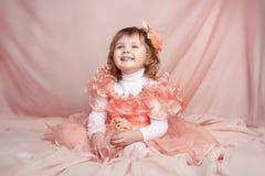 Glückliches lächelndes lustiges kleines Mädchen, das oben über Drapierung schaut Stockfoto