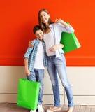 Glückliches lächelndes Mutter- und Sohnkind mit den Einkaufstaschen, die Spaß haben Stockfotos