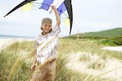 Glückliches Little Boy, das Drachen über Kopf auf Strand hält Lizenzfreie Stockfotos