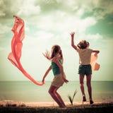 Glückliches Mädchen, das auf den Strand springt Lizenzfreies Stockfoto