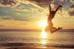 Glückliches Mädchen, das auf den Strand springt Stockfotos