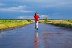 Glückliches Mädchen, das auf nasser Straße läuft Stockfotos