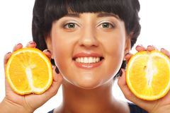 Glückliches Mädchen, das Orangen über Gesicht hält Stockbilder