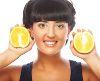 Glückliches Mädchen, das Orangen über Gesicht hält Stockfotografie