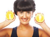 Glückliches Mädchen, das Orangen über Gesicht hält Stockfotos