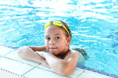 Glückliches Mädchen mit Schutzbrillen im Swimmingpool Stockfoto